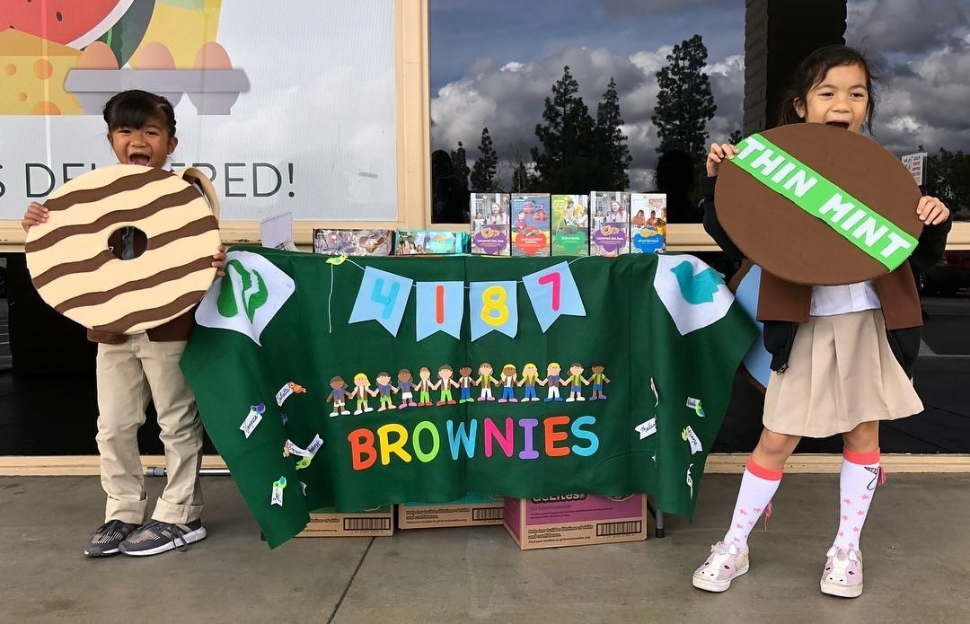Girl scout brownies Malana Pascual(left) and Mikaela Saengdara from troop 4187 in Fullerton invite shoppers to visit their cookie booth outside a local grocery store